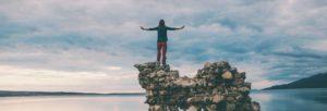 Frau balanciert auf Steinen am Meer