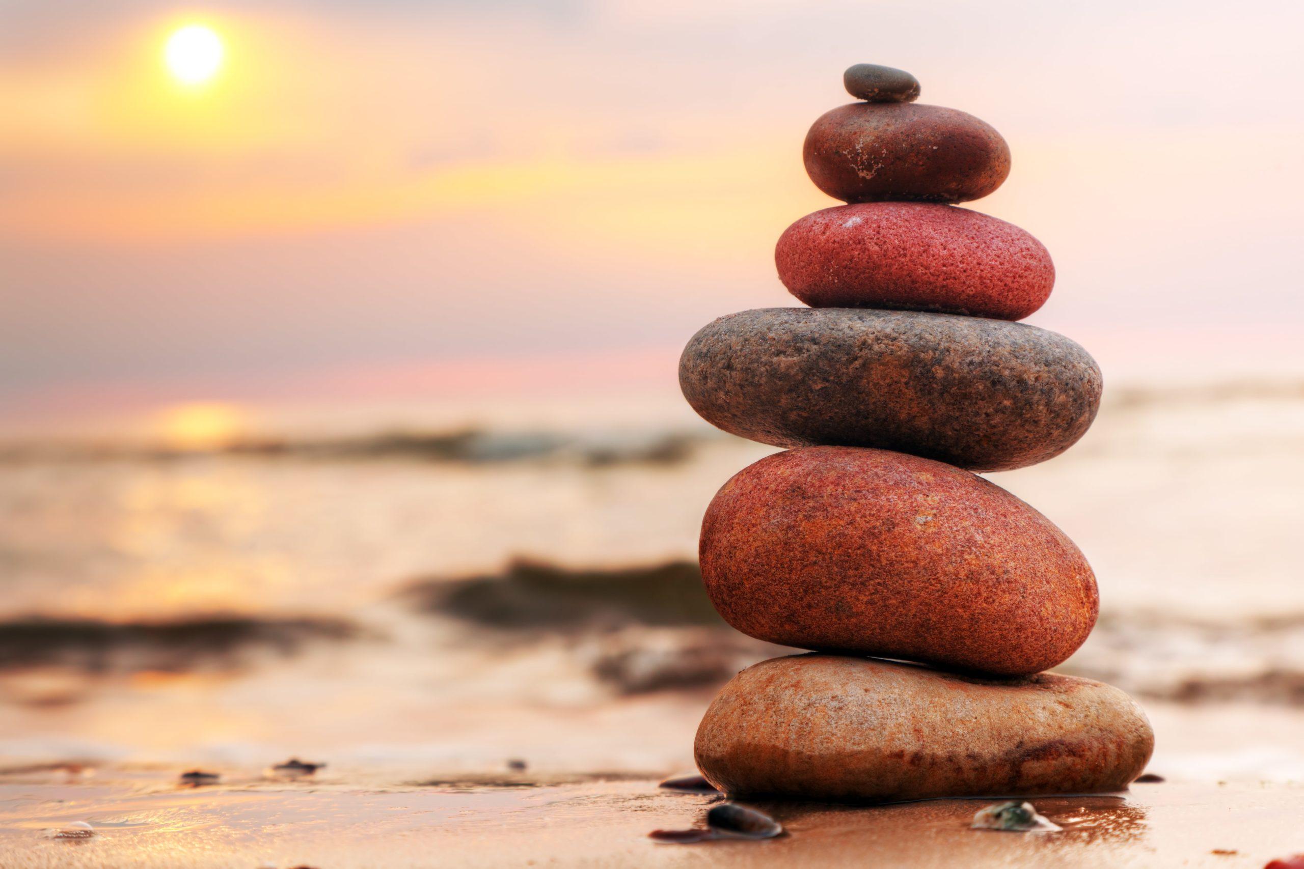 Ein Stapel Steine am Strand bei Sonnenuntergang als Symbol für das Gleichgewicht der Hormone