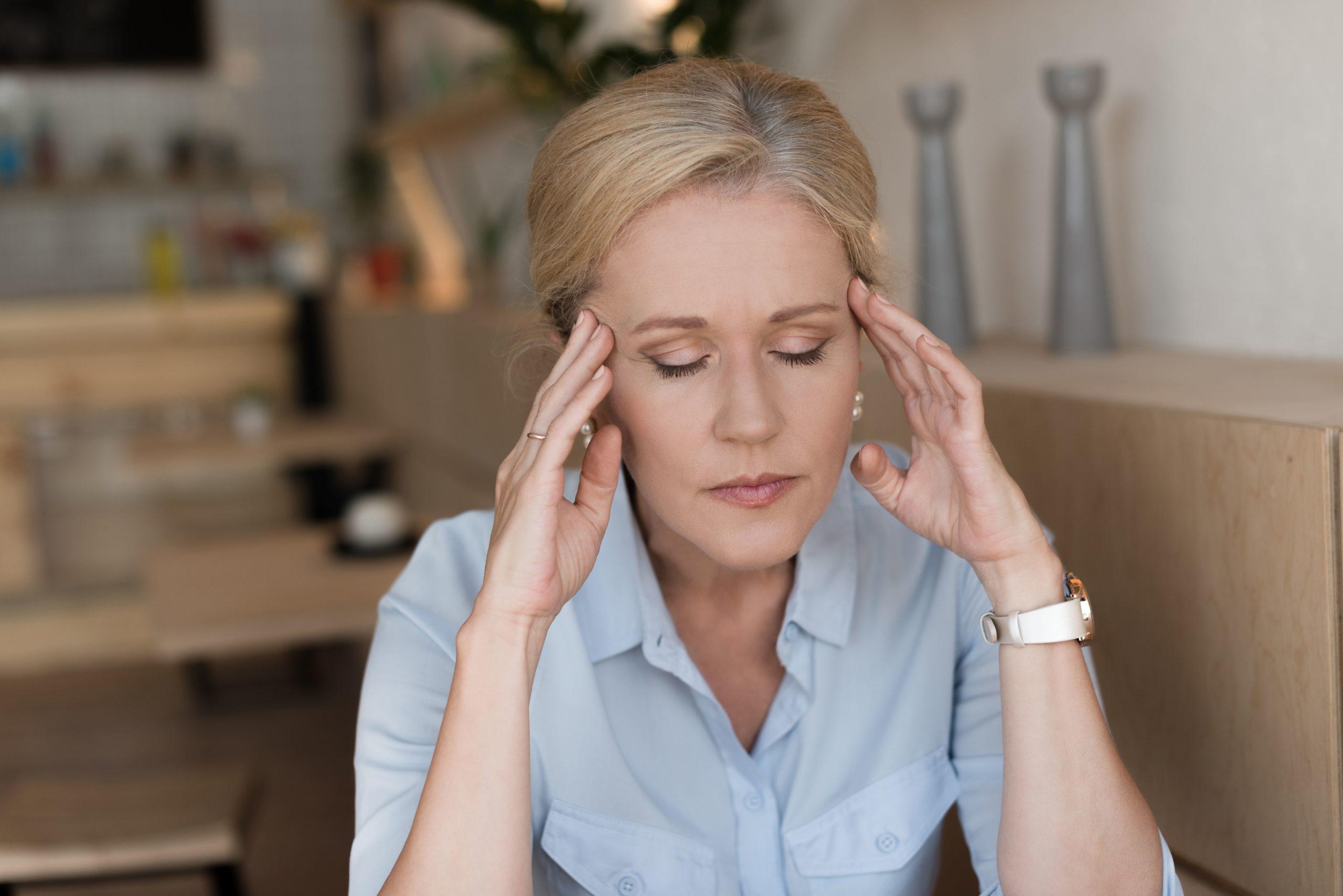 Frau hat ihre Hände an den Schläfen. Sie sieht gestresst aus.