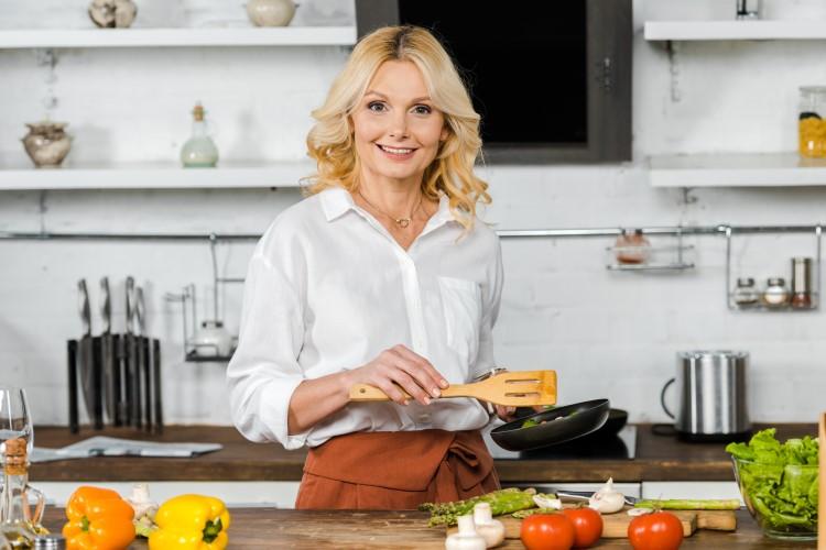 Frau kocht Pfanne mit Tomaten und Champignons