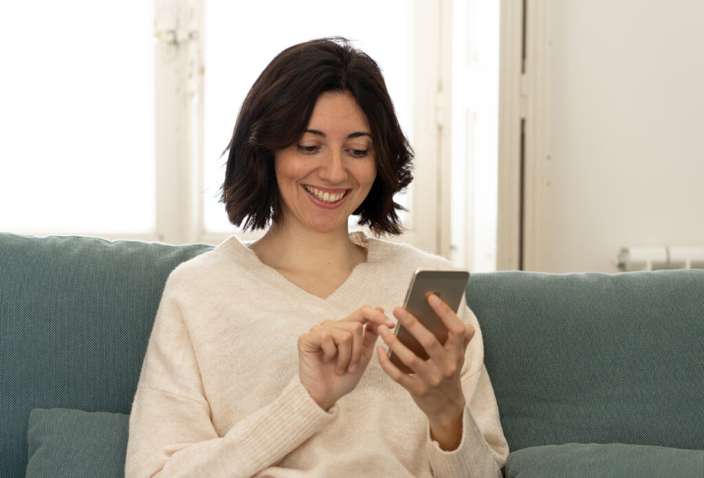 happy young woman using her smart phone sitting on sofa at home. in leisure and mobile addiction